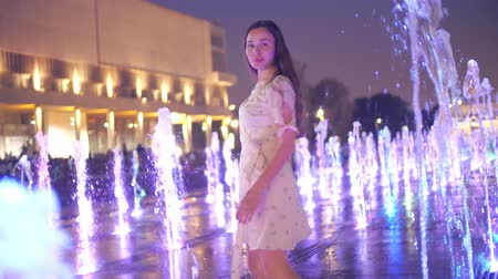 nemli : Beautiful young woman dances in the illuminated fountain in the evening, slow motion