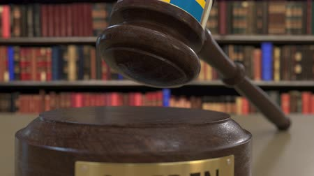 jurisdiction : Flag of Sweden on falling judges gavel in court. National justice or jurisdiction related conceptual 3D animation Stock Footage