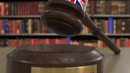 jurisdiction : Flag of Great Britain on falling judges gavel in court. National justice or jurisdiction related conceptual 3D animation