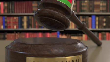 árverezői kalapács : Flag of Azerbaijan on falling judges gavel in court. National justice or jurisdiction related conceptual 3D animation Stock mozgókép