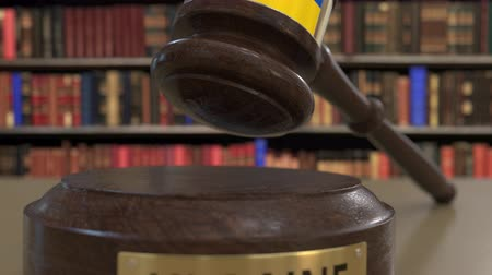 jurisdiction : Flag of Ukraine on falling judges gavel in court. National justice or jurisdiction related conceptual 3D animation