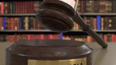 jurisdiction : Flag of Indonesia on falling judges gavel in court. National justice or jurisdiction related conceptual 3D animation Stock Footage