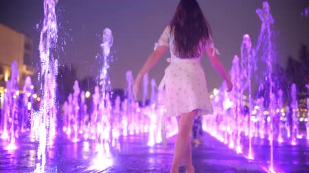 pace : Slim young woman in dress walks in the fountain in the evening, slow motion shot