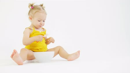 smudged : Little blonde baby girl eats her breakfast against white background