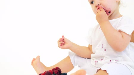 smudged : Funny baby girl eats berries against white background Stock Footage