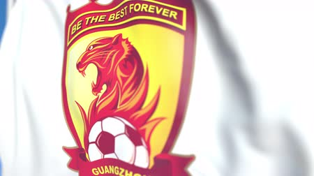soar : Flying flag with Guangzhou Evergrande Taobao FC football club logo, close-up. Editorial loopable 3D animation Stock Footage