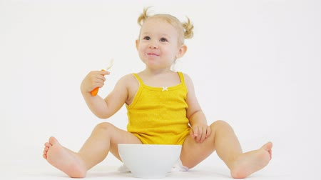 smudged : Happy baby girl eating her oatmeal on white background