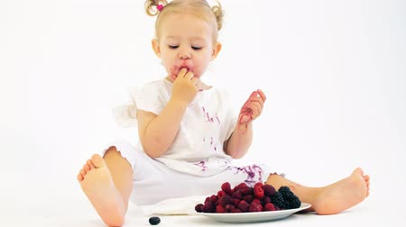 smudged : Adorable baby girl eating fresh juicy berries on white background