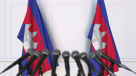 cambojano : Cambodian official press conference. Flags of Cambodia and microphones. Conceptual 3D animation