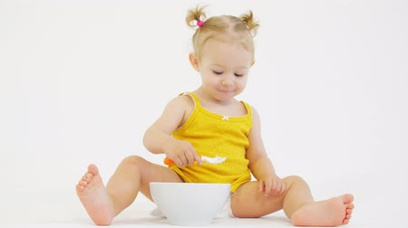 zabkása : Happy blonde baby girl eats her oatmeal against white background