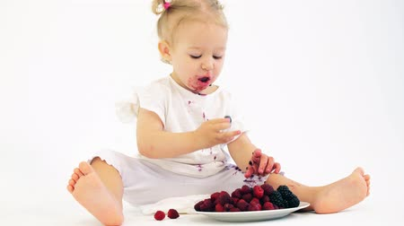 seçenekleri : Blonde baby girl eating berries against white background Stok Video