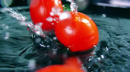 wetness : Fresh red tomatoes splash and roll on water, slow motion shot Stock Footage