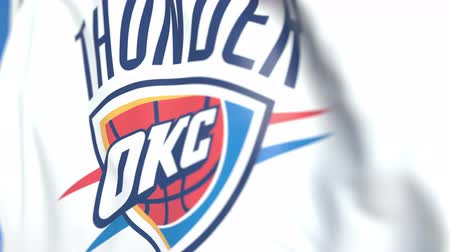 гром : Waving flag with Oklahoma City Thunder team logo, close-up. Editorial loopable 3D animation
