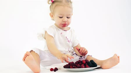 smudged : Smudged baby girl eats berries against white background