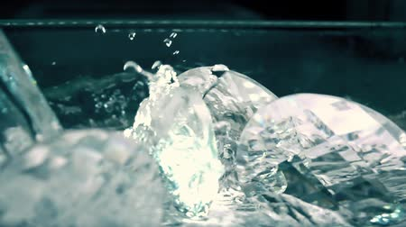 refractive : Slow motion shot of water being poured over glass crystals