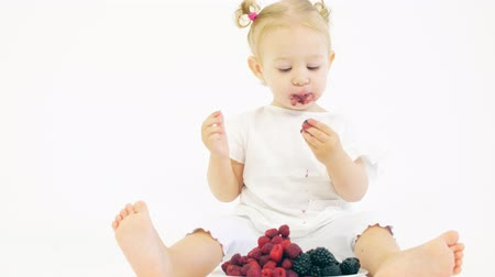 zwarte bes : Baby girl eating fresh berries on white background Stockvideo