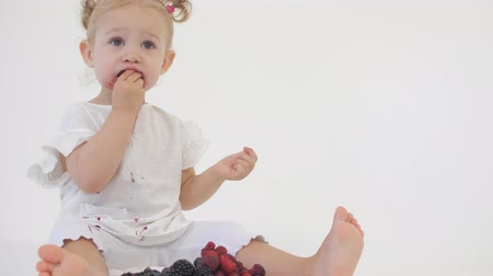 smudged : Baby girl in white clothes eats juicy berries on light background