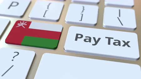 taxatie : PAY TAX text and flag of Oman on the computer keyboard. Taxation related conceptual 3D animation Stockvideo
