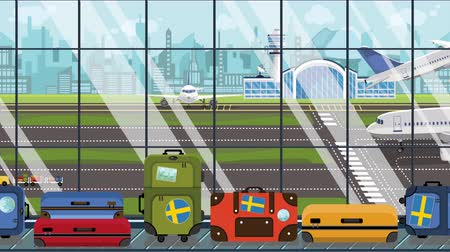 svéd : Suitcases with Sweden flag stickers on baggage carousel in airport. Swedish tourism conceptual loopable cartoon animation