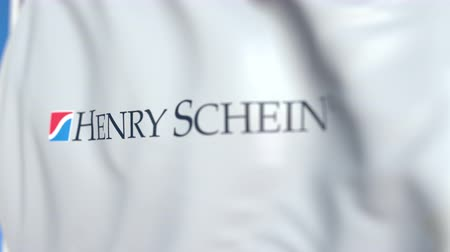 flapping : Waving flag with Henry Schein logo, close-up. Editorial loopable 3D animation Stock Footage