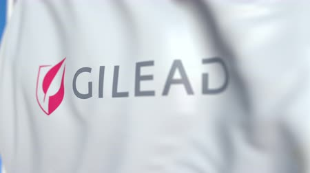 companhia : Waving flag with Gilead Sciences logo, close-up. Editorial loopable 3D animation