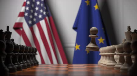 estratégico : Flags of United States and EU behind chess board. The first pawn moves in the beginning of the game. Political rivalry conceptual 3D animation