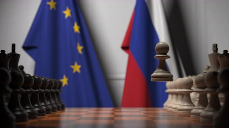 oposto : Flags of the EU and Russia behind chess board. The first pawn moves in the beginning of the game. Political rivalry conceptual 3D animation