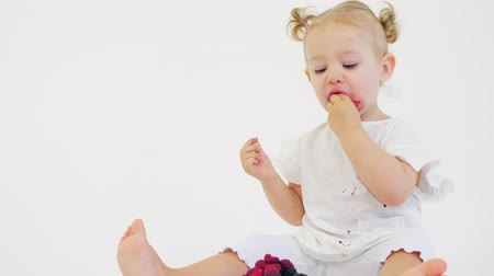 オプション : Baby girl eats fresh raspberries and blackberries against white background