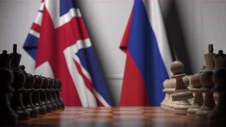 pieza de ajedrez : Flags of the UK and Russia behind chess board. The first pawn moves in the beginning of the game. Political rivalry conceptual 3D animation Archivo de Video