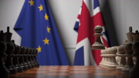 pedina : Flags of the EU and the UK behind chess board. The first pawn moves in the beginning of the game. Brexit related conceptual 3D animation