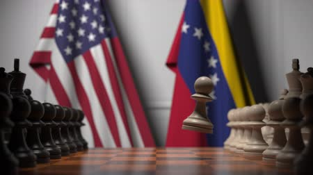 pieza de ajedrez : Flags of United States and Venezuela behind chess board. The first pawn moves in the beginning of the game. Political rivalry conceptual 3D animation Archivo de Video