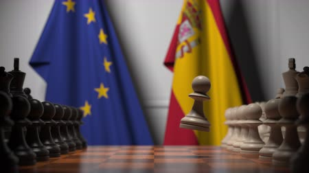 estratégico : Flags of the EU and Spain behind chess board. The first pawn moves in the beginning of the game. Political rivalry conceptual 3D animation