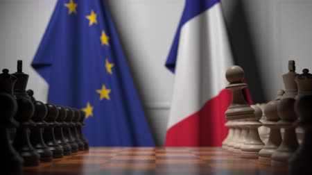 oposto : Flags of the EU and France behind chess board. The first pawn moves in the beginning of the game. Political rivalry conceptual 3D animation Stock Footage