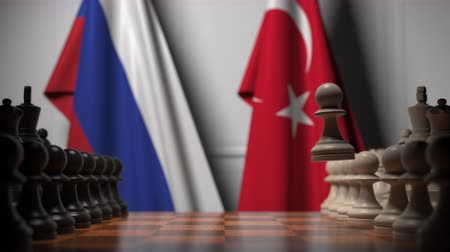 pedina : Flags of Russia and Turkey behind chess board. The first pawn moves in the beginning of the game. Political rivalry conceptual 3D animation
