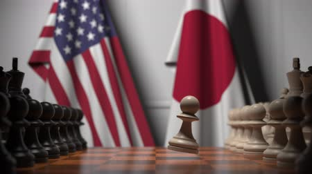 pieza de ajedrez : Flags of United States and Japan behind chess board. The first pawn moves in the beginning of the game. Political rivalry conceptual 3D animation