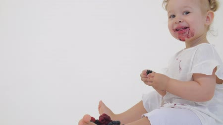 amoras : Happy baby girl eats juicy berries on light background