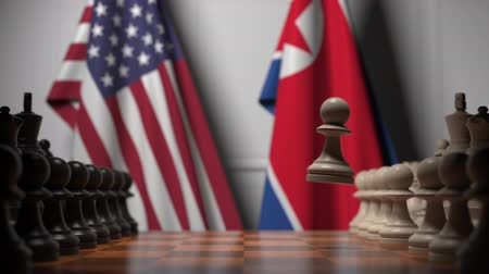 dprk : Flags of the USA and North Korea behind chess board. The first pawn moves in the beginning of the game. Political rivalry conceptual 3D animation