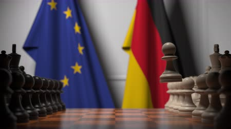 peão : Flags of the EU and Germany behind chess board. The first pawn moves in the beginning of the game. Political rivalry conceptual 3D animation