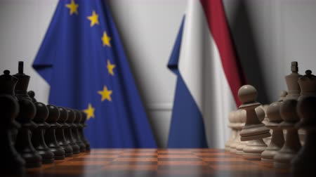 šachy : Flags of the EU and the Netherlands behind chess board. The first pawn moves in the beginning of the game. Political rivalry conceptual 3D animation