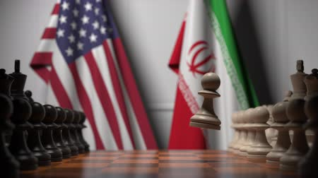 estratégico : Flags of United States and Iran behind chess board. The first pawn moves in the beginning of the game. Political rivalry conceptual 3D animation Vídeos