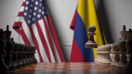 соперничество : Flags of United States and Colombia behind chess board. The first pawn moves in the beginning of the game. Political rivalry conceptual 3D animation