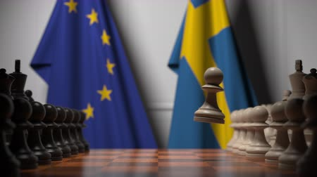 pedina : Flags of the EU and Sweden behind chess board. The first pawn moves in the beginning of the game. Political rivalry conceptual 3D animation Filmati Stock