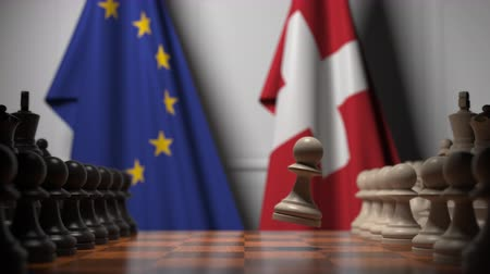 peão : Flags of the EU and Switzerland behind chess board. The first pawn moves in the beginning of the game. Political rivalry conceptual 3D animation