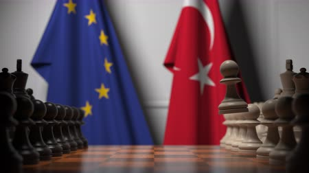 pieza de ajedrez : Flags of the EU and Turkey behind chess board. The first pawn moves in the beginning of the game. Political rivalry conceptual 3D animation