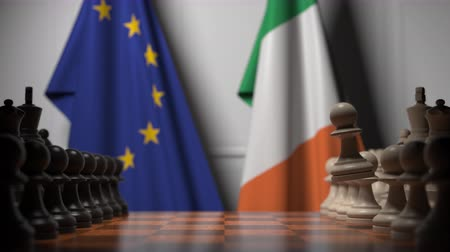 стратегический : Flags of the EU and the Republic of Ireland behind chess board. The first pawn moves in the beginning of the game. Political rivalry conceptual 3D animation Стоковые видеозаписи