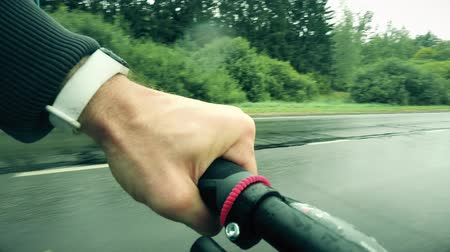 endure : POV cycling shot. Mans hand on a bike grip while riding along rural road on a rainy day