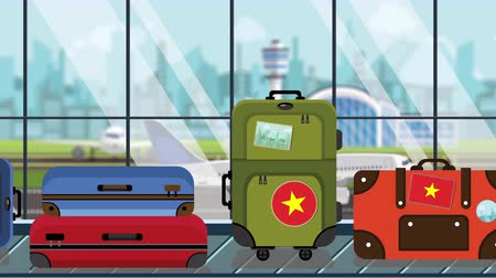 istek : Suitcases with Vietnamese flag stickers on baggage carousel in airport, close-up. Tourism in Vietnam related loopable cartoon animation