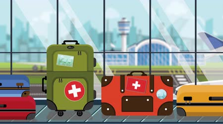 toon : Suitcases with Swiss flag stickers on baggage carousel in airport, close-up. Tourism in Switzerland related loopable cartoon animation