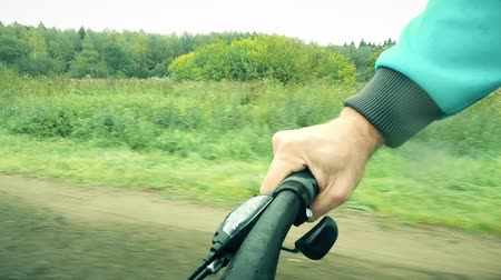 úmido : POV cycling shot. Mans hand on a bicycle grip and shifter while riding along forest road on a rainy day Vídeos