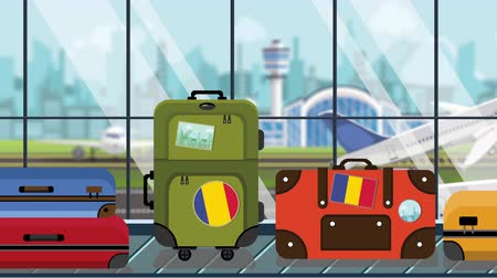 istek : Suitcases with Romanian flag stickers on baggage carousel in airport, close-up. Tourism in Romania related loopable cartoon animation